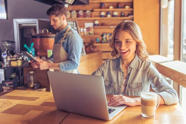 Belle jeune femme sourit en travaillant avec un ordinateur portable. Photo Premium