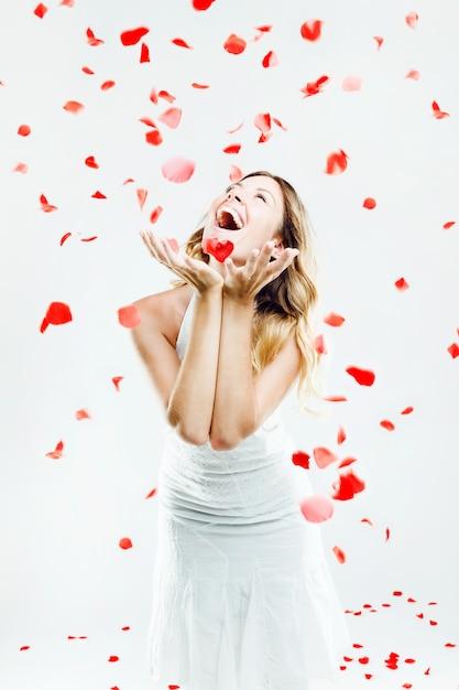 Belle jeune femme sous une pluie de pétales de rose. isolé sur blanc. Photo gratuit