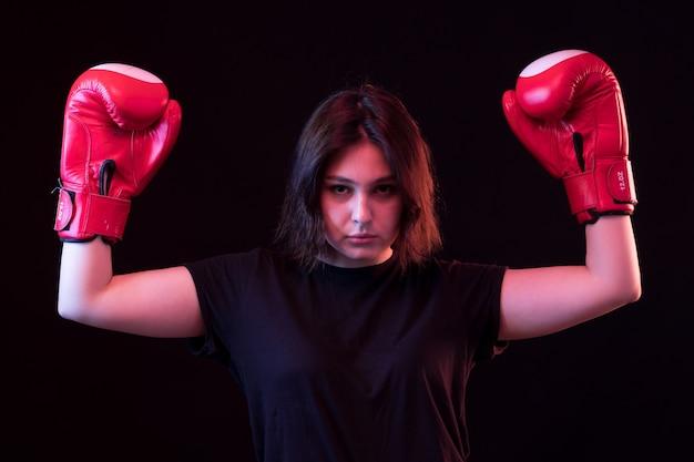 Belle Jeune Femme En T-shirt Noir Et Gants De Boxe Rouges Photo gratuit