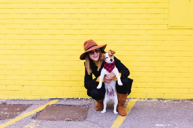 Belle jeune femme tenant et aimant son chien. mur de brique jaune amour et animaux domestiques dehors Photo Premium