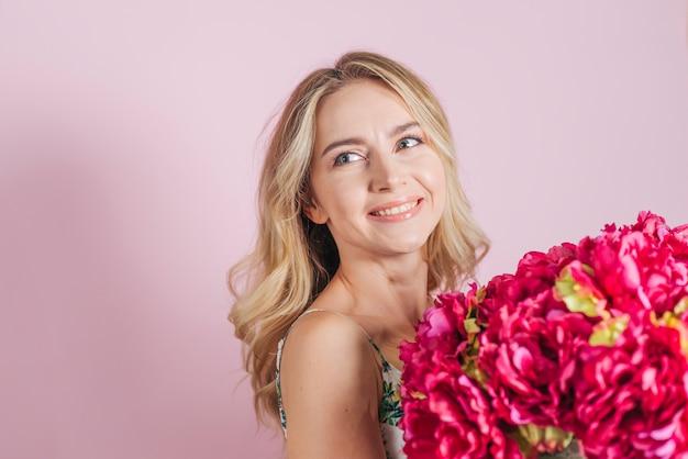 Belle Jeune Femme Tenant Un Bouquet De Roses Sur Fond Rose Photo gratuit