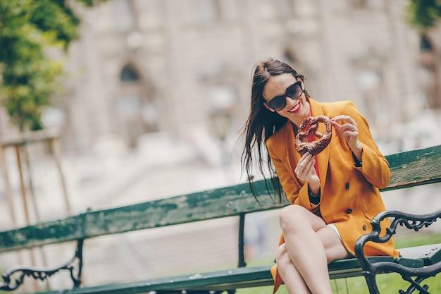 Belle jeune femme tenant un bretzel et se détendre dans le parc Photo Premium