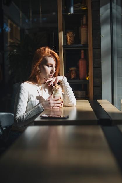 Belle jeune femme tenant un pot de smoothie au café Photo gratuit