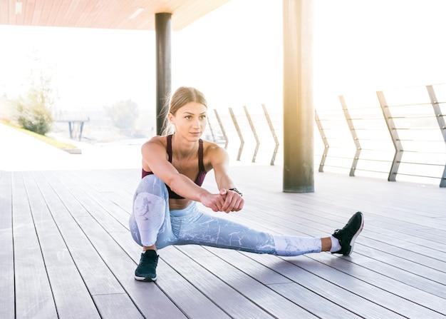 Belle jeune femme en tenue de sport faisant des exercices d'étirement Photo gratuit
