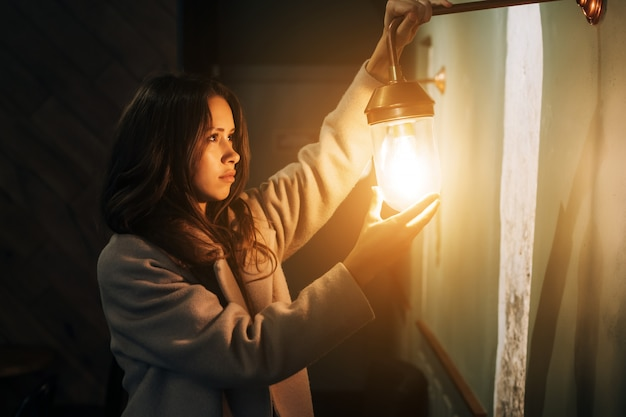 Belle jeune femme tient dans sa main une petite lampe murale Photo gratuit