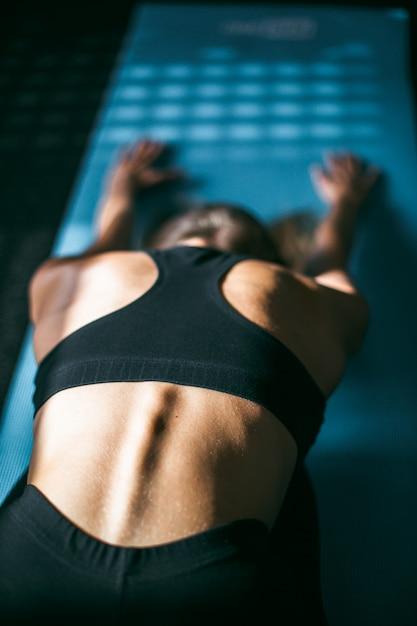 Belle jeune femme travaillant dans la salle de gym, faire des exercices de yoga plié vers l'avant sur tapis bleu Photo Premium
