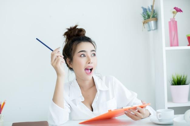 Belle jeune femme travaillant sur son ordinateur portable dans sa chambre. Photo gratuit