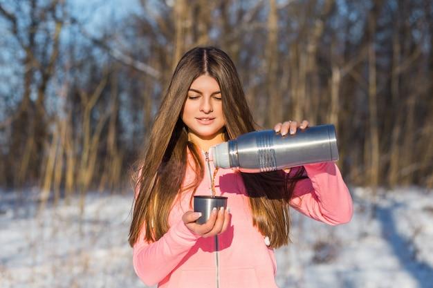 Belle jeune femme verse du thé Photo Premium