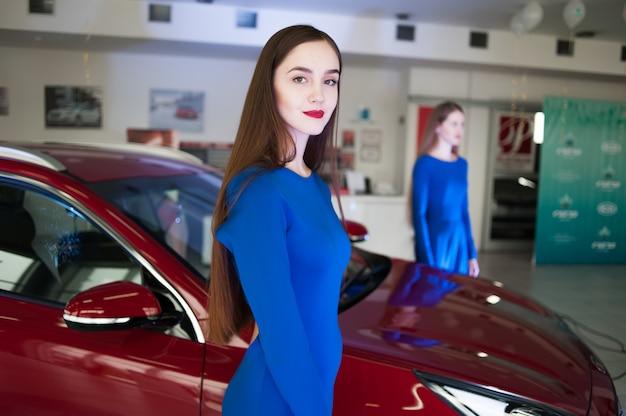 Belle Jeune Femme Vêtue D'une Robe Au Salon De L'automobile Photo Premium