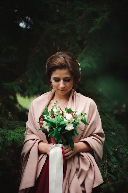 La belle jeune femme vêtue d'une robe de mariée avec un bouquet Photo Premium