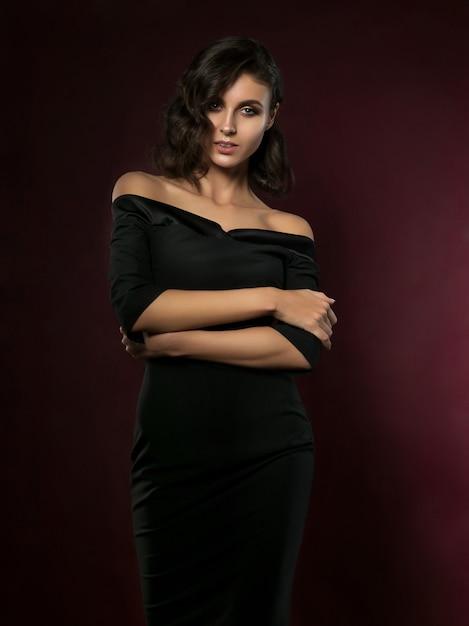 Belle Jeune Femme Vêtue D'une Robe De Soirée Noire Posant Sur Fond Rouge Foncé Photo Premium