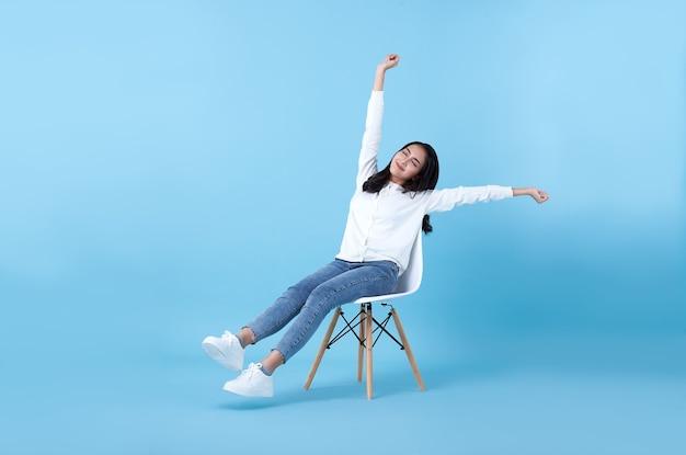 Belle Jeune Fille Asiatique Souriante Se Détendre Assis Sur Une Chaise Sur Bleu. Photo gratuit