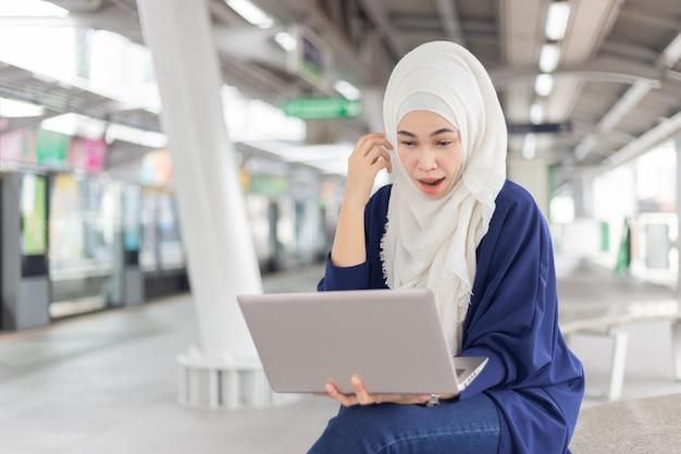 Belle jeune fille asiatique travaillant dans un skytrain avec un ordinateur portable. femmes musulmanes Photo Premium