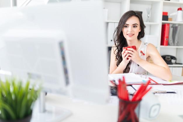 Belle jeune fille assise au bureau, regarde l'écran d'ordinateur et tient une tasse rouge dans les mains. Photo Premium