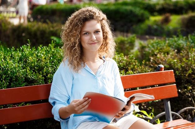 Jeune femme assise sur un banc de parc — Photographie