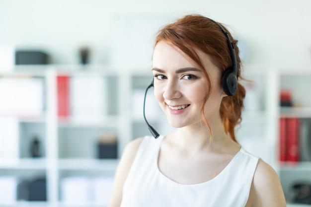 Belle jeune fille au casque avec microphone debout dans le bureau Photo Premium
