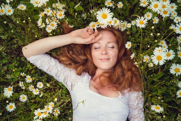 Belle jeune fille aux cheveux roux bouclés dans le champ de camomille Photo Premium