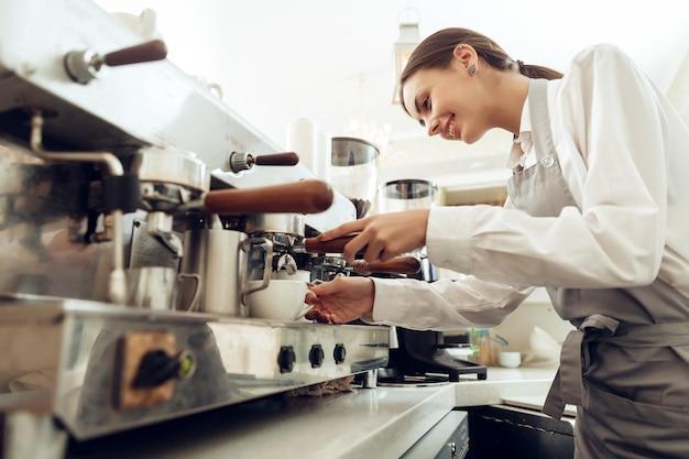 Belle jeune fille barista préparant un café Photo Premium