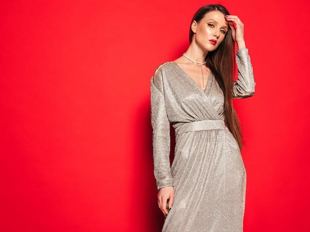 Belle Jeune Fille Brune Dans Une Belle Robe D'été à La Mode.sexy Femme Insouciante Posant Près Du Mur Rouge En Studio.modèle à La Mode Avec Le Maquillage De Soirée Lumineux Photo gratuit
