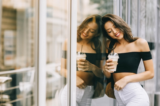 Belle jeune fille buvant du café dans la ville Photo Premium