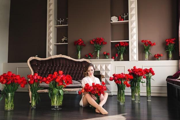 Une Belle Jeune Fille Dans Un Peignoir Est Assise Par Terre Dans Le Salon Entre De Grands Bouquets De Tulipes. Concept 8 Mars. Photo Premium