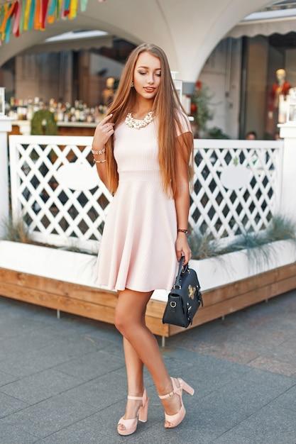 Belle Jeune Fille Avec Un Doux Sourire Dans Une Robe Rose Avec Sac à Main Marchant Dans La Ville Photo Premium