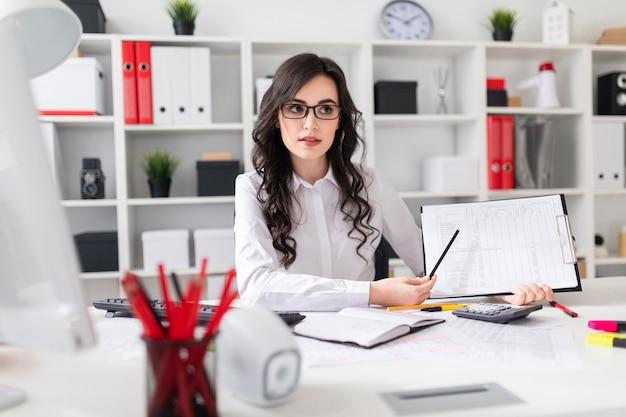 Une belle jeune fille est assise à une table dans le bureau et pointe un crayon sur les informations contenues dans le document. Photo Premium