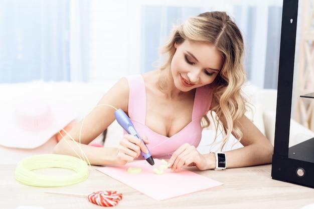 Une belle jeune fille expérimente un stylo 3d. Photo Premium