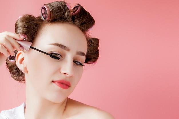 Belle Jeune Fille Joyeuse Dans Le Bigoudi Peint Un Sourcil Sur L'espace Rose Photo Premium
