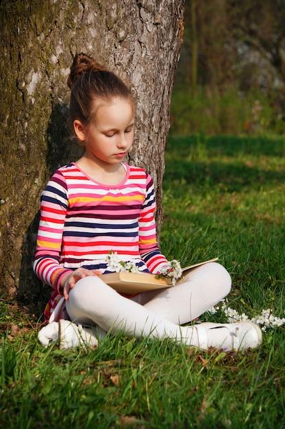 Belle jeune fille lit un livre dans le parc, assis sur l'herbe près de l'arbre Photo Premium