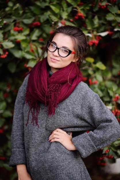 Belle Jeune Fille Avec Des Lunettes Et Une écharpe Bordeaux Sur Une Surface D'un Arbre Avec Des Fruits Rouges Photo Premium