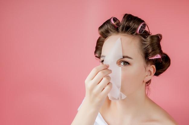 Belle jeune fille avec un masque et des bigoudis touchant son visage. Photo Premium