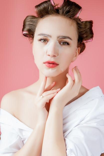 Belle Jeune Fille Avec Un Masque Et Des Bigoudis Touchant Son Visage Photo Premium
