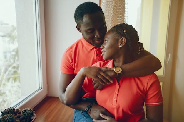 Une belle jeune fille noire dans un t-shirt rose et un jean bleu debout à la maison près de la fenêtre Photo gratuit