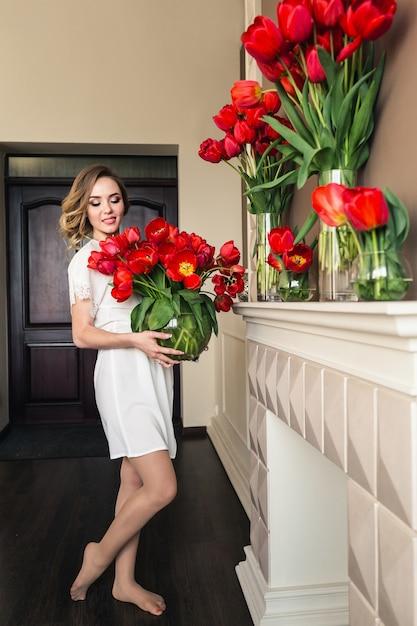 Une Belle Jeune Fille En Peignoir Tient Dans Ses Mains Beaucoup De Tulipes Rouges Dans Un Vase. Concept Du 8 Mars. Photo Premium