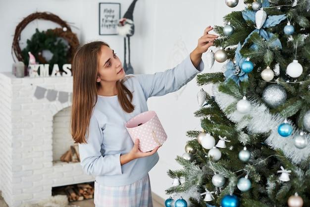 Belle Jeune Fille En Pyjama Décorant Le Sapin De Noël Photo Premium