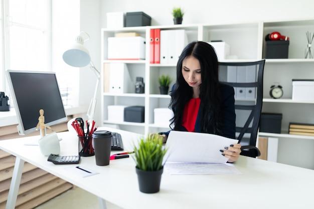 Belle jeune fille regarde à travers des documents, assis dans le bureau à la table Photo Premium