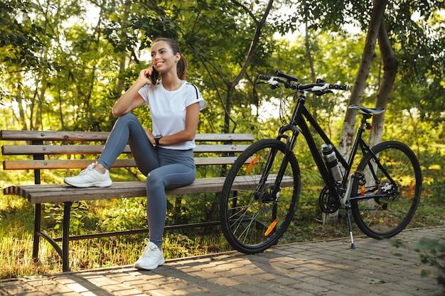 Belle Jeune Fille De Remise En Forme Assise Sur Un Banc à Vélo Dans Le Parc Photo Premium