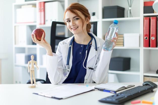 Une belle jeune fille en robe blanche est assise à une table dans le bureau et tient une pomme et une bouteille d'eau à la main. Photo Premium