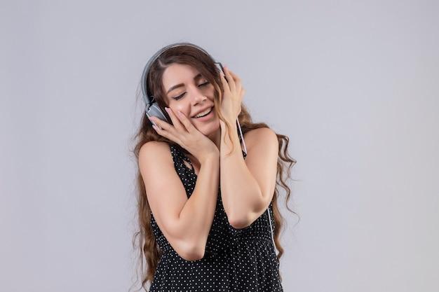 Belle Jeune Fille En Robe à Pois Appréciant La Musique Préférée Grâce à Des écouteurs Sans Fil Debout Avec Les Yeux Fermés Sur Fond Blanc Photo gratuit