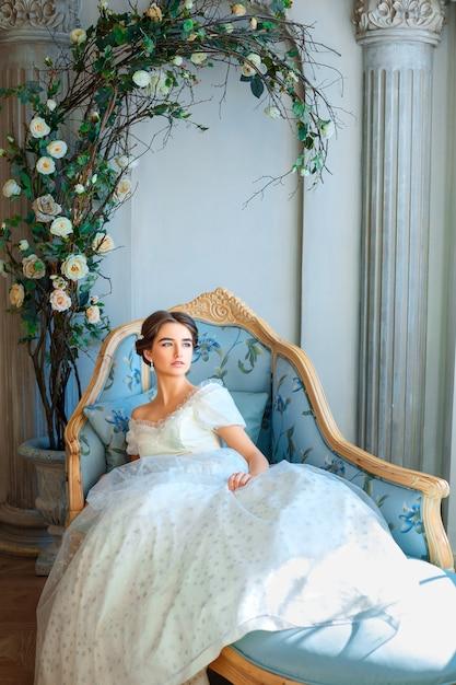 Belle jeune fille en robe riche, allongé sur le canapé, se détendre concept Photo Premium
