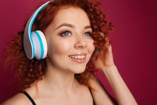 Belle jeune fille rousse aux cheveux bouclés avec un casque. portrait en gros plan Photo Premium