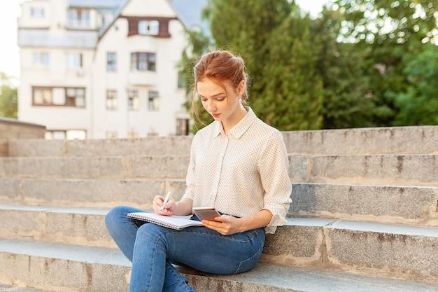 Belle jeune fille rousse avec des taches de rousseur assis sur un escalier Photo Premium