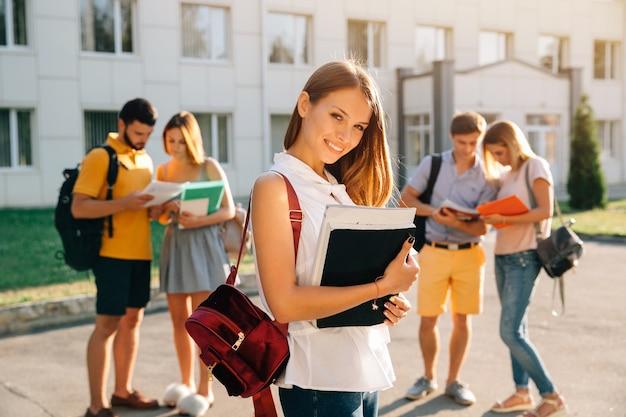 Belle jeune fille avec sac à dos de velours rouge, tenant des livres Photo gratuit