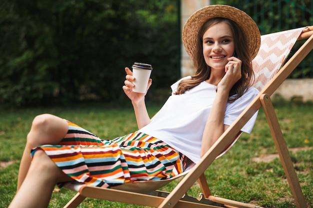 Belle Jeune Fille Se Reposant Sur Un Hamac Au Parc De La Ville à L'extérieur En été, Boire Du Café à Emporter, Parler Au Téléphone Mobile Photo Premium