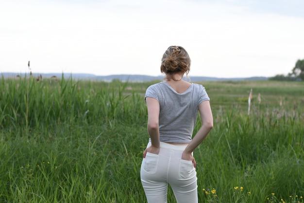 Belle jeune fille se reposant sur une soirée d'été dans la nature et dans la ville Photo Premium