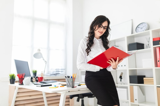 Belle jeune fille se tient dans le bureau, se penchant sur le bureau et fait défiler dossier rouge avec des documents Photo Premium