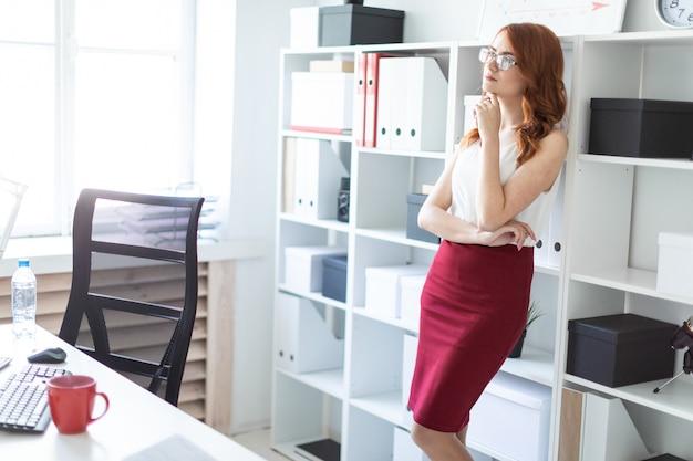 Belle jeune fille se trouve dans le bureau près d'une étagère avec des documents Photo Premium