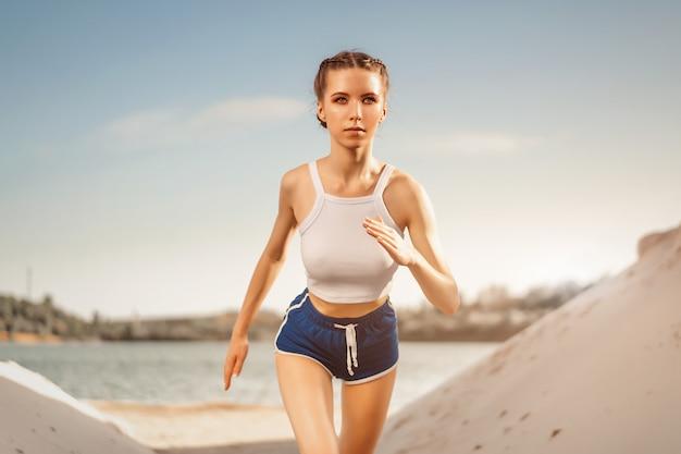 Belle jeune fille sportive sexy en cours d'exécution le matin d'été nature. la femme travaille au bord du lac. mode de vie sain. entraînement de fitness en plein air. Photo Premium