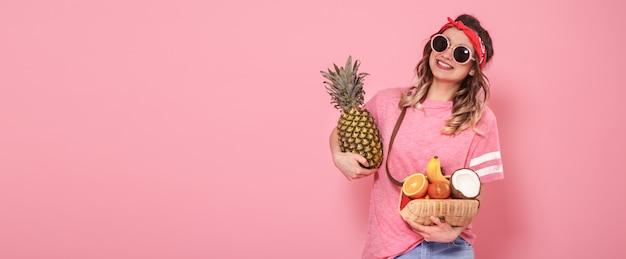 Belle Jeune Fille En T-shirt Rose Et Lunettes, Détient Un Sac De Paille Plein De Fruits Sur Fond Rose Photo gratuit